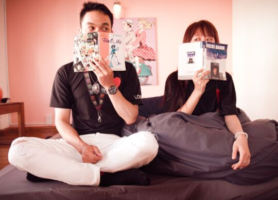 couple-holding-books-sitting-on-bed-1057015