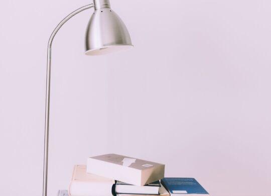 silver-desk-lamp-near-pile-of-books-1122530